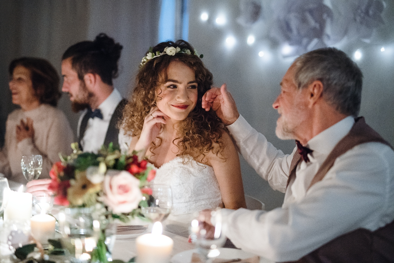 father of the bride with his hand on the brides cheek at the wedding dinner table