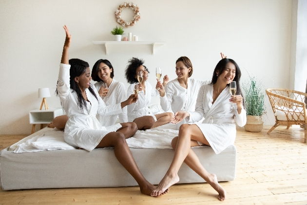 female friends in bath robes on a bed