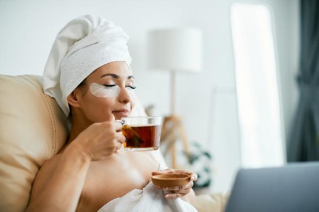 woman in bath tub with tea and eye mask