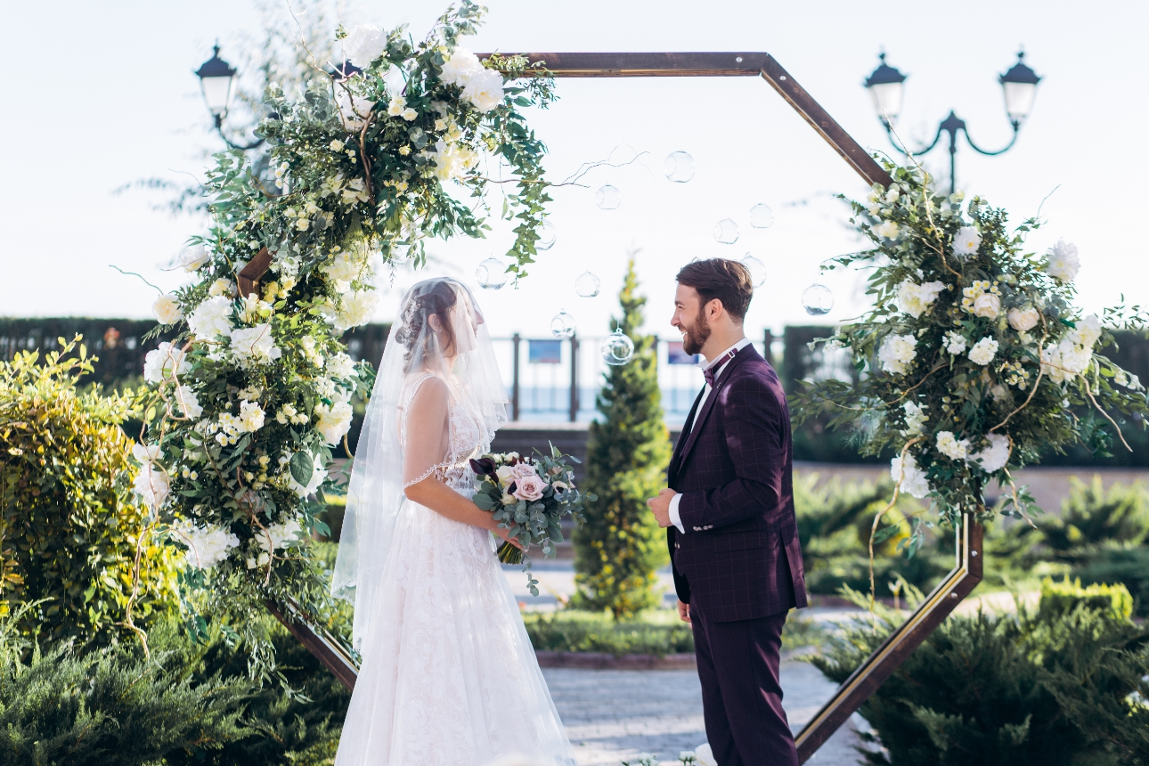 couple in front of a floral moongate on their wedding day